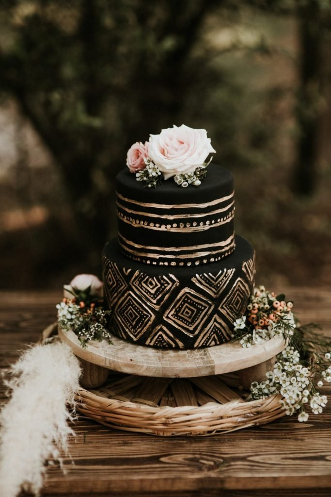 gold and black wedding cake with pink flowers on top