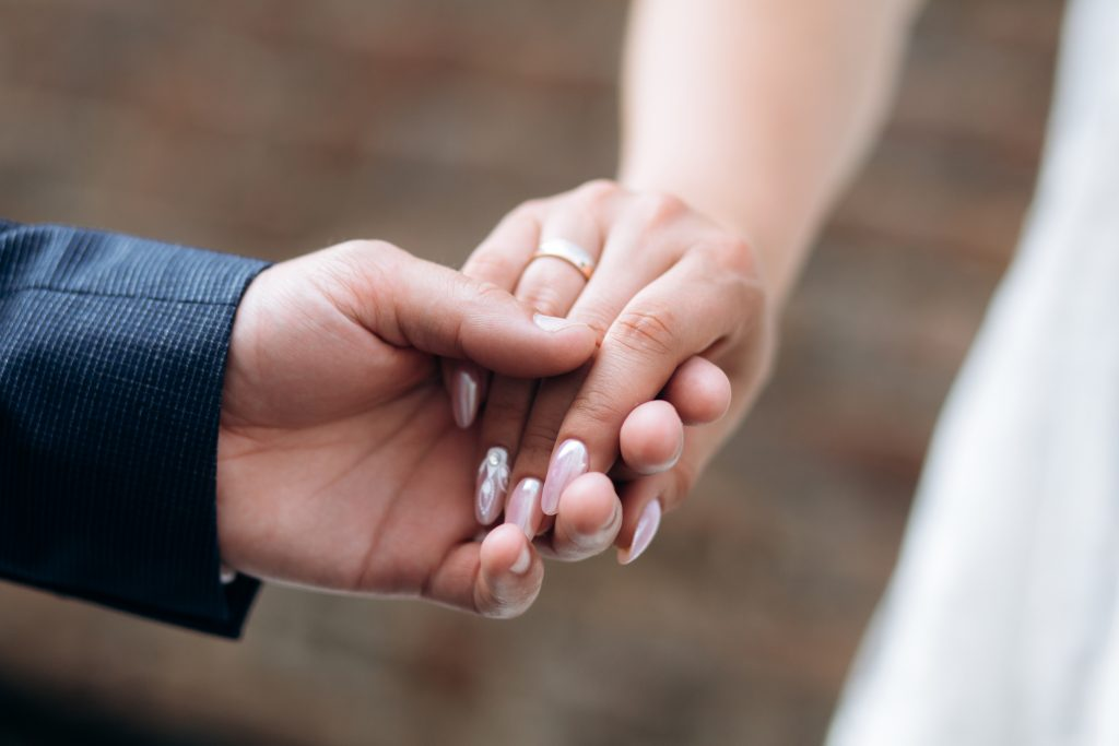 couple holding hands with rings