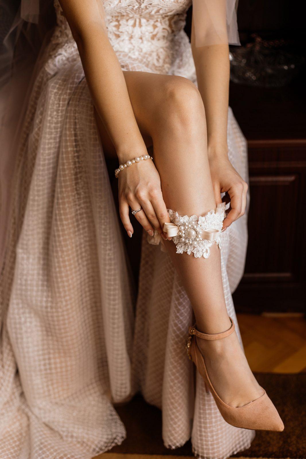 bride puts wedding garter on right leg