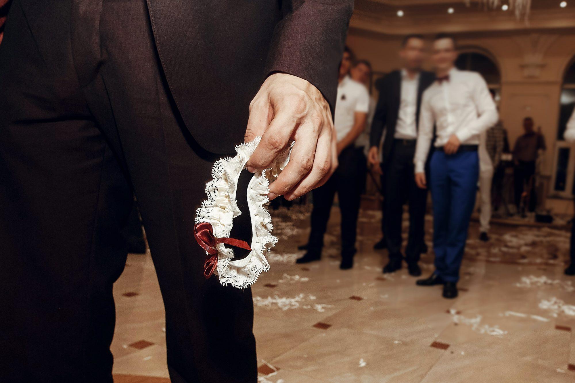 groom holds bride's wedding garter for toss