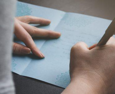 woman writing anniversary card
