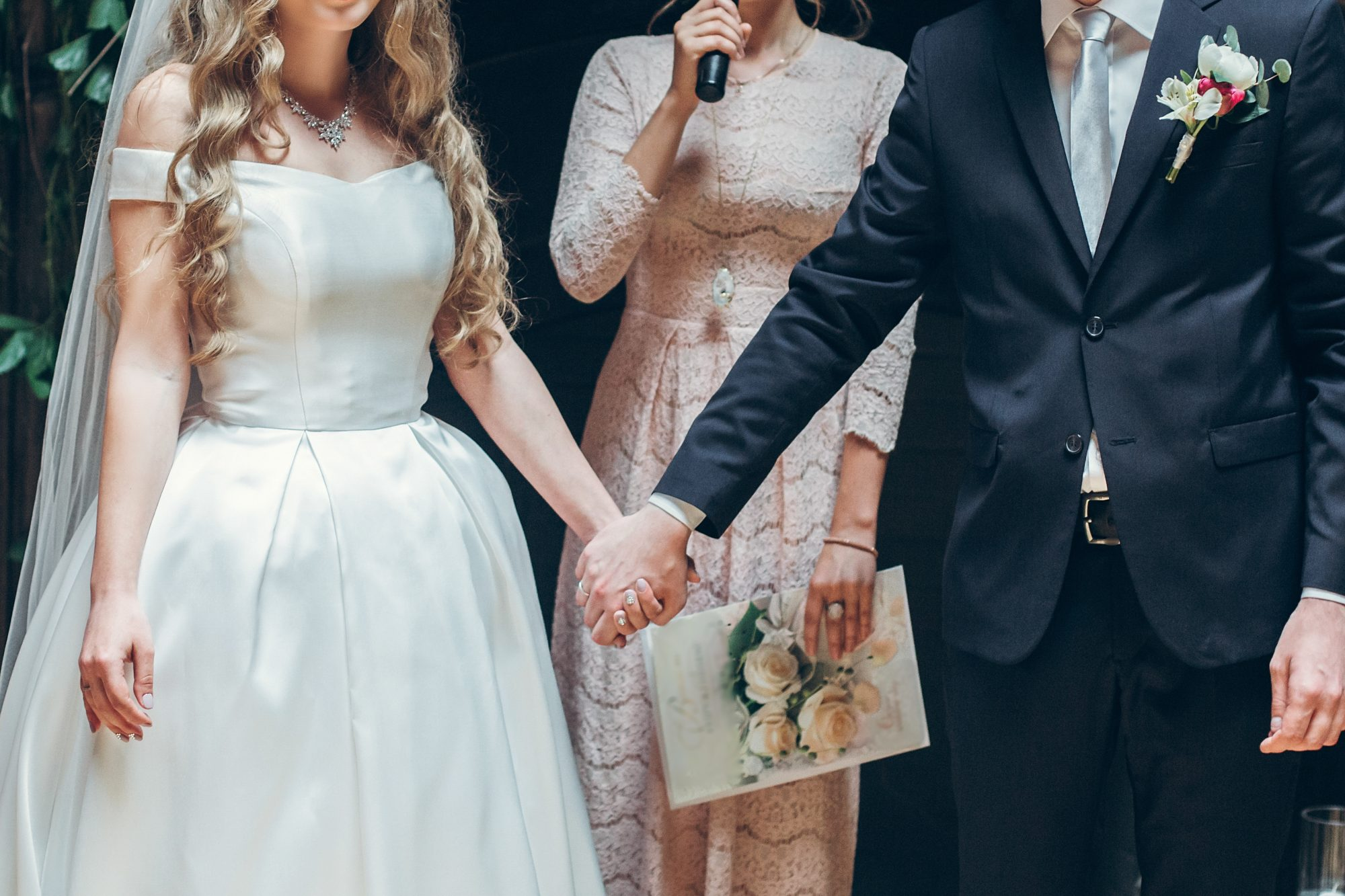 bride, groom, and wedding officiant talking