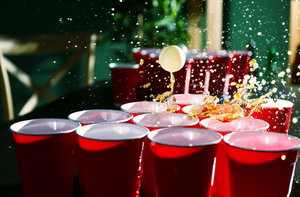 ping pong ball landing in cup of beer