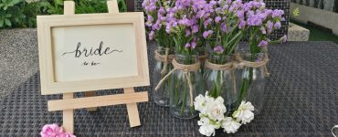 wooden bride to be sign next to purple wildflowers in jars