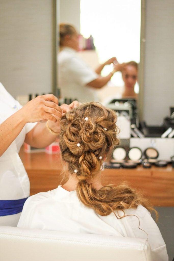 hairstylist styling woman's wedding hair