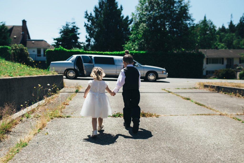 ring bearer and flower girl hold hands as they walk towards a limo to go to wedding