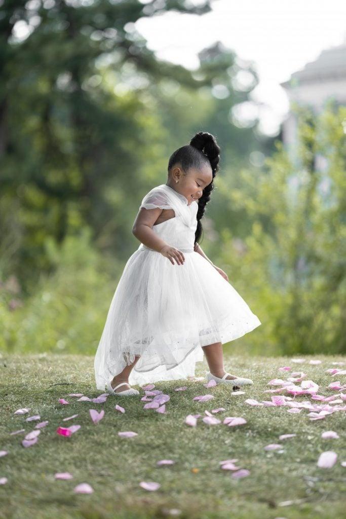 little girl in wedding dress stepping on flower petal pathway