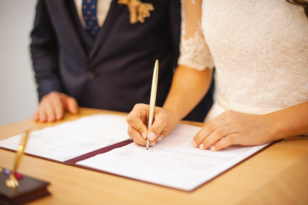 husband and wife signing marriage license