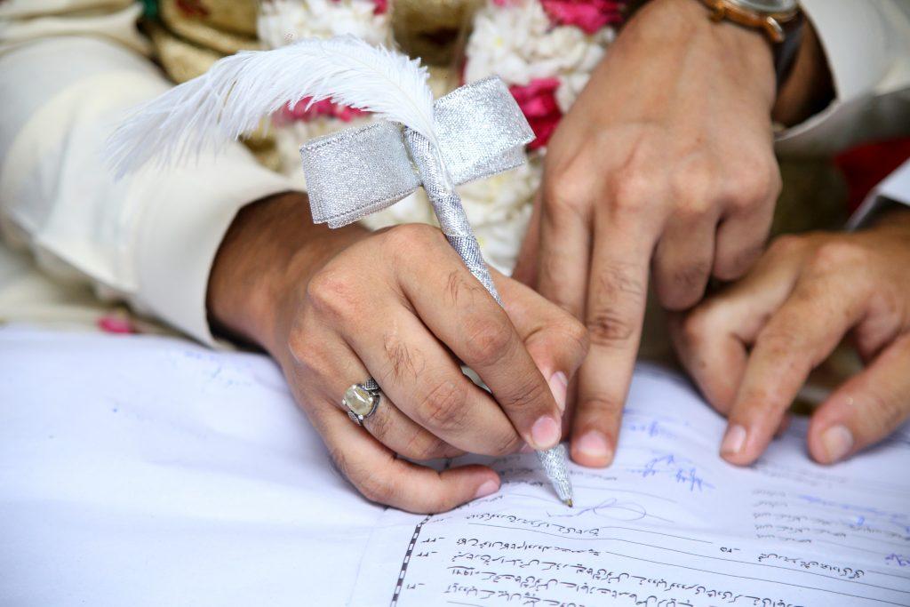 man and woman signing wedding license