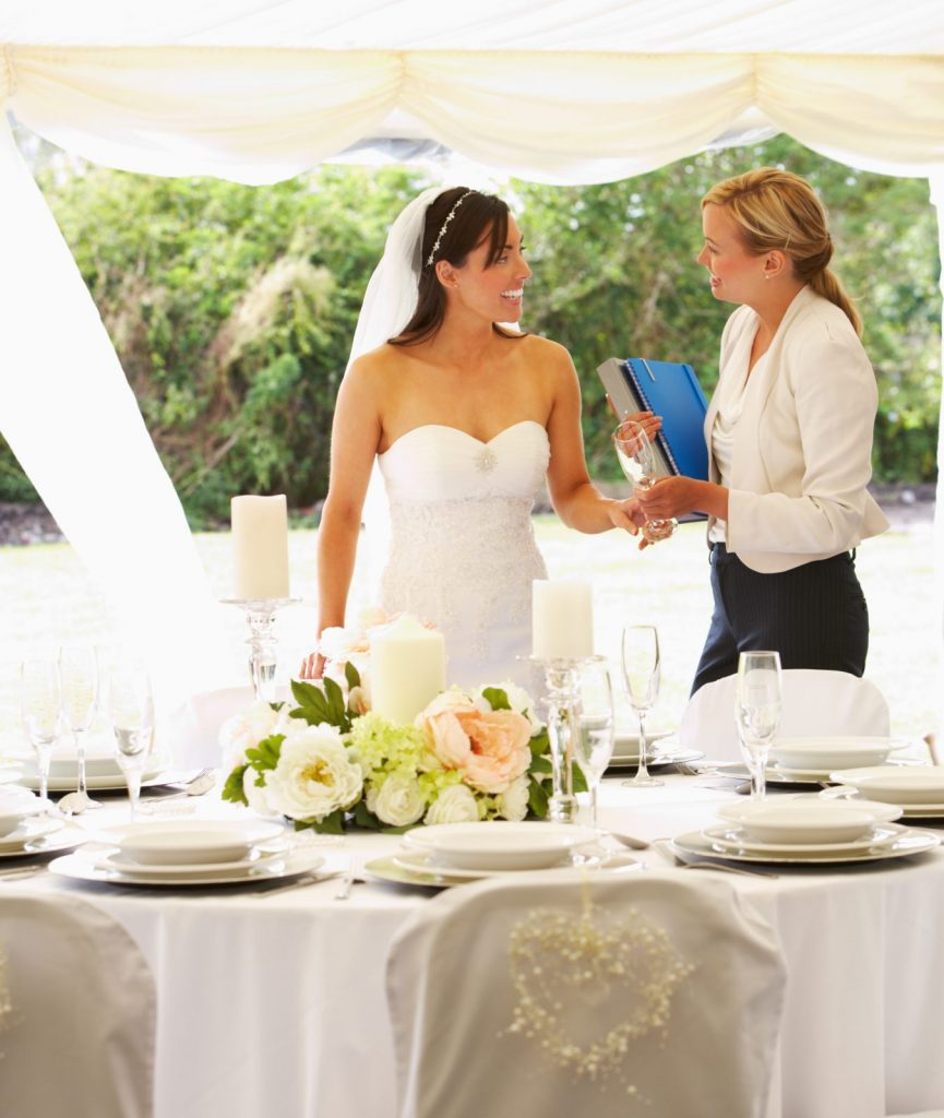 wedding planner with bride at wedding reception