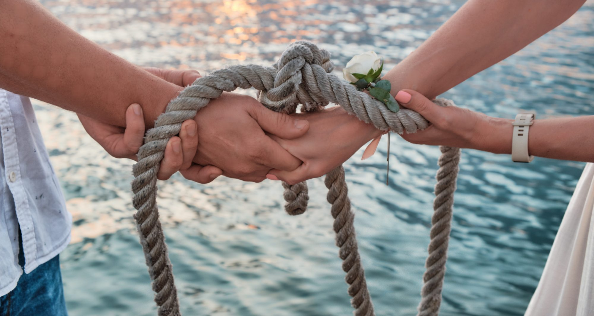couple's hands tied with rope at handfasting ceremony by the beach