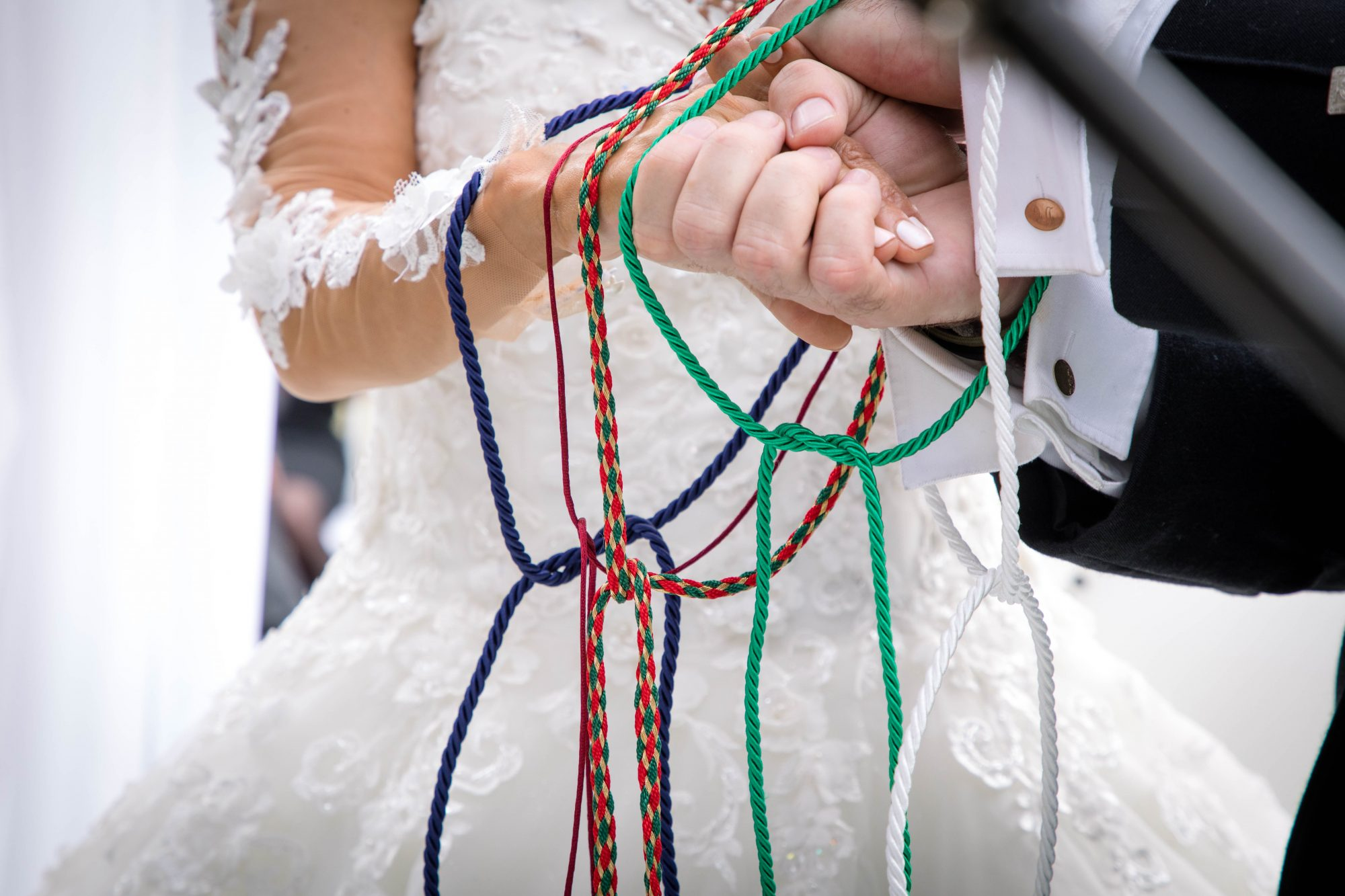 couple's hands tied at wedding ceremony