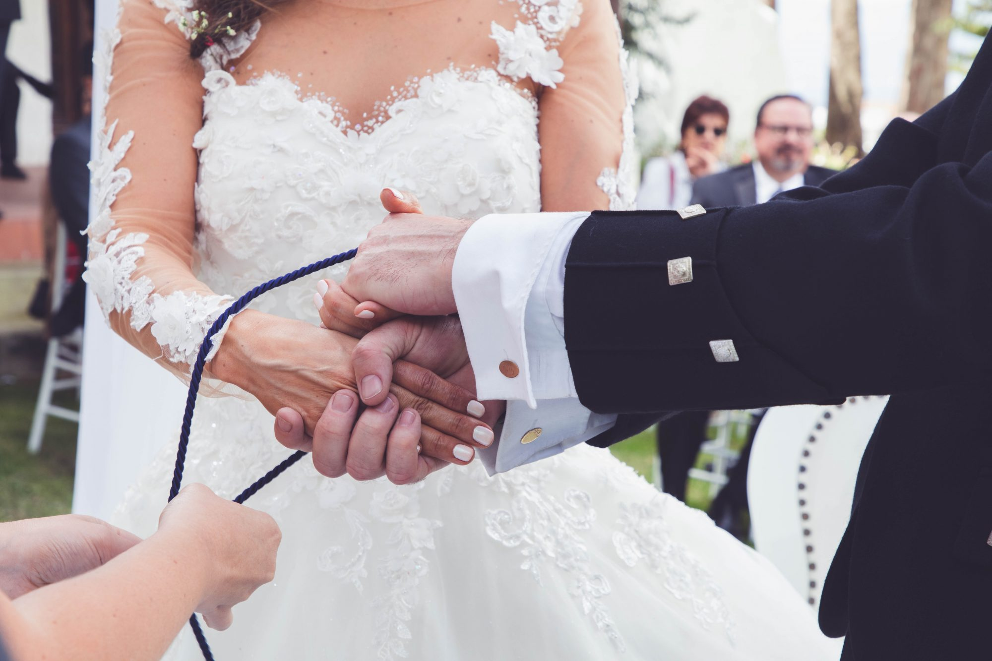 couple's hands being tied with purple cord at wedding