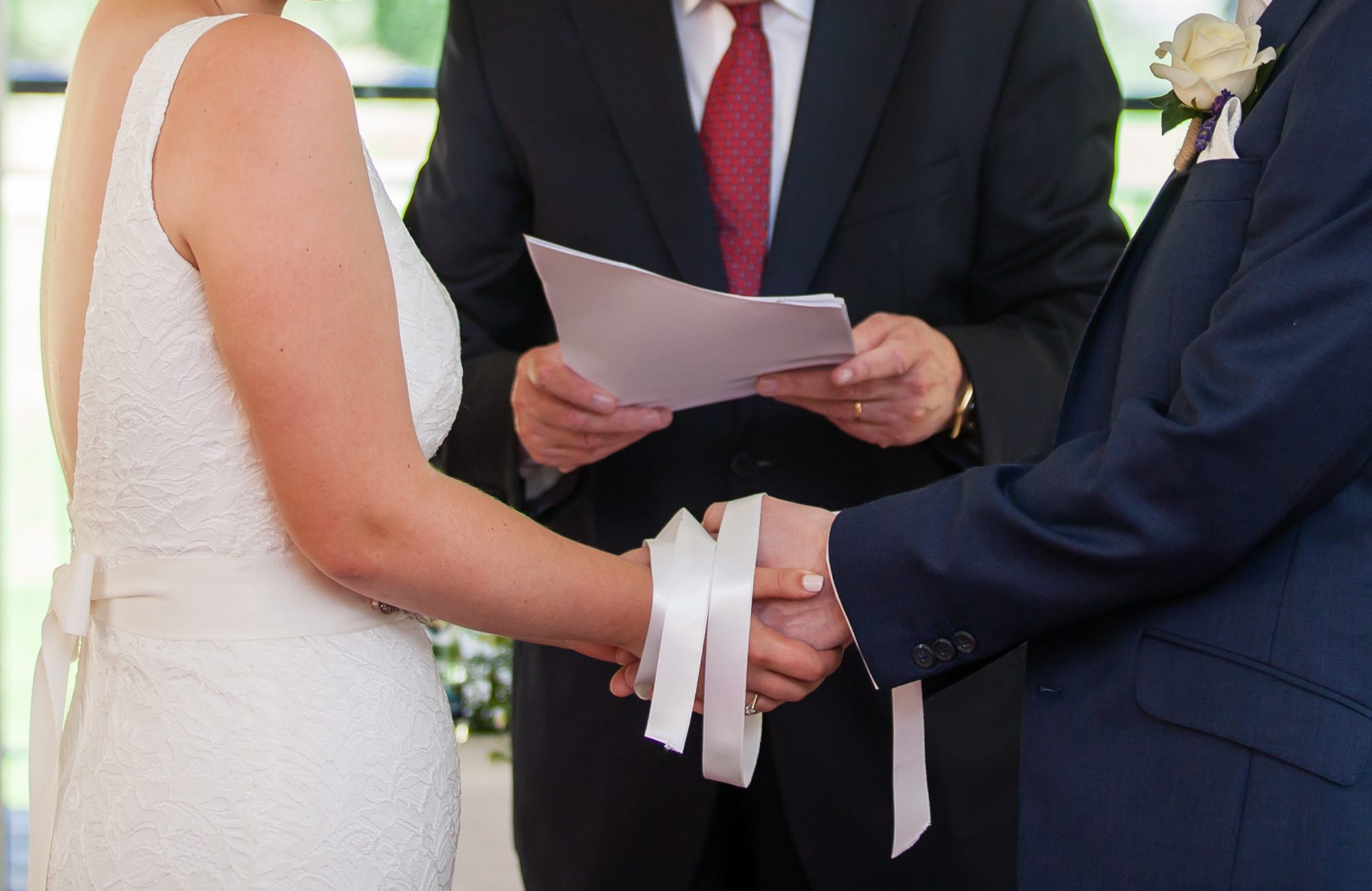 bride and groom's hands tied with white ribbons