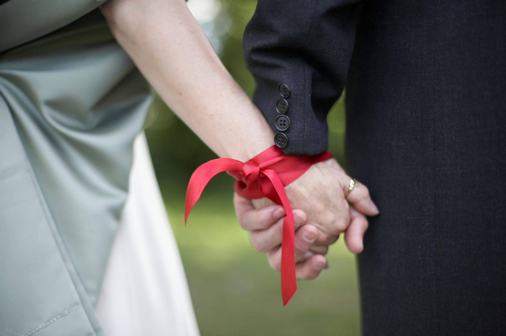 Couple's hands tied with red ribbon