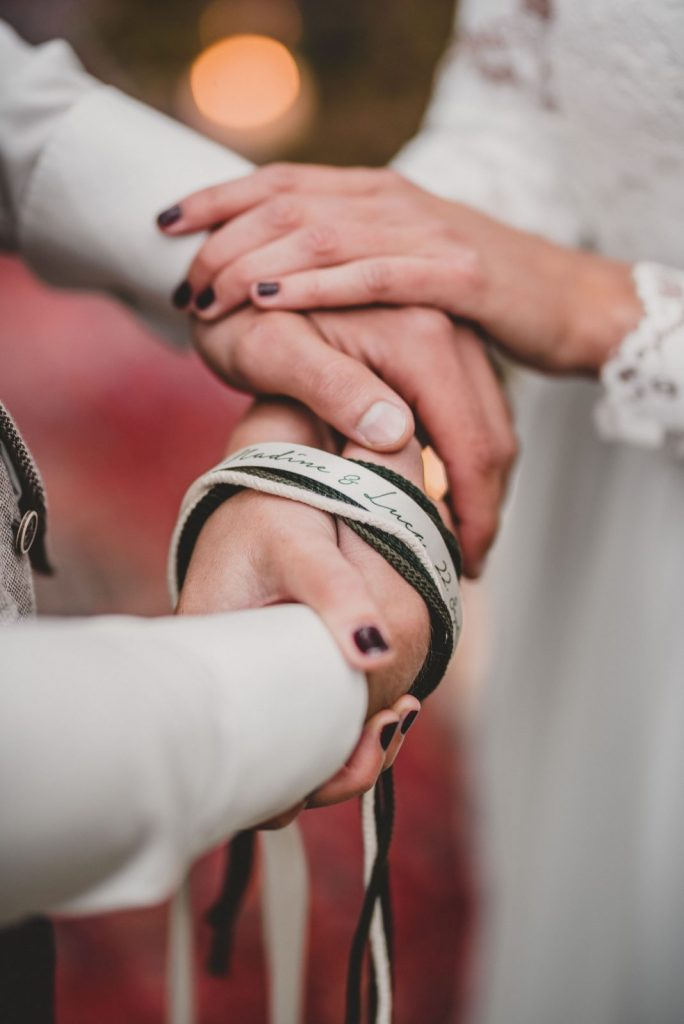 couple's hands tied with cords