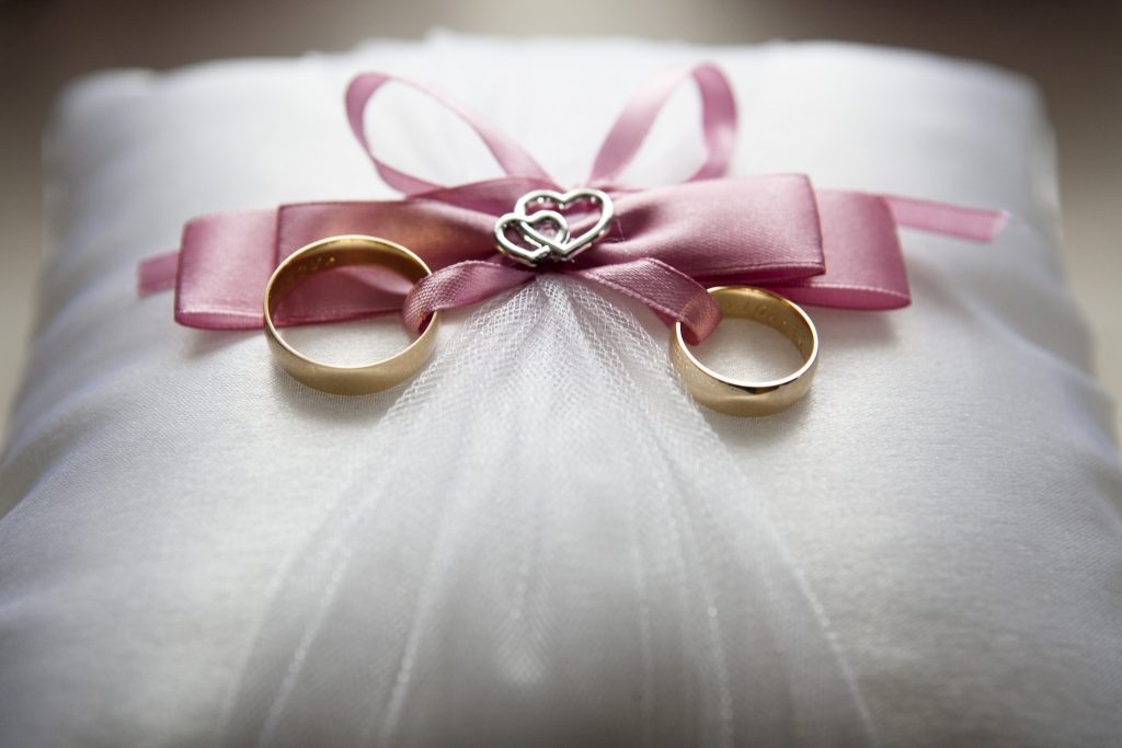 pink ribbon with wedding rings tied to it