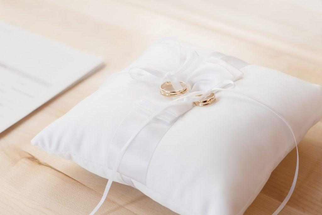 wedding rings on white pillow