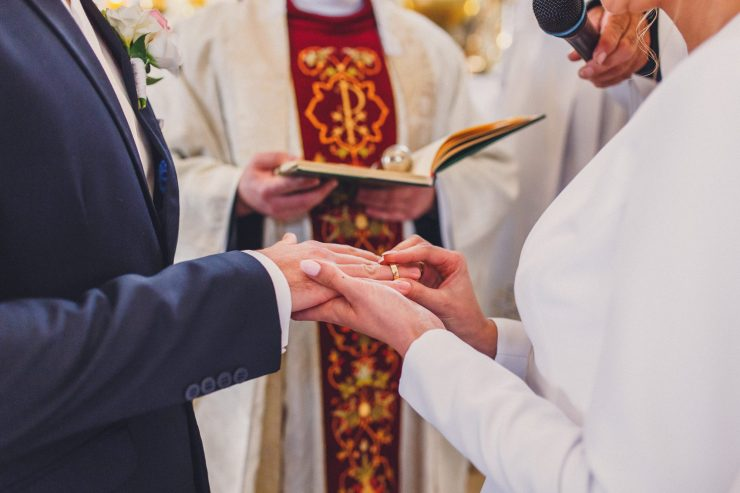Bride and groom and priest at traditional Polish wedding ceremony