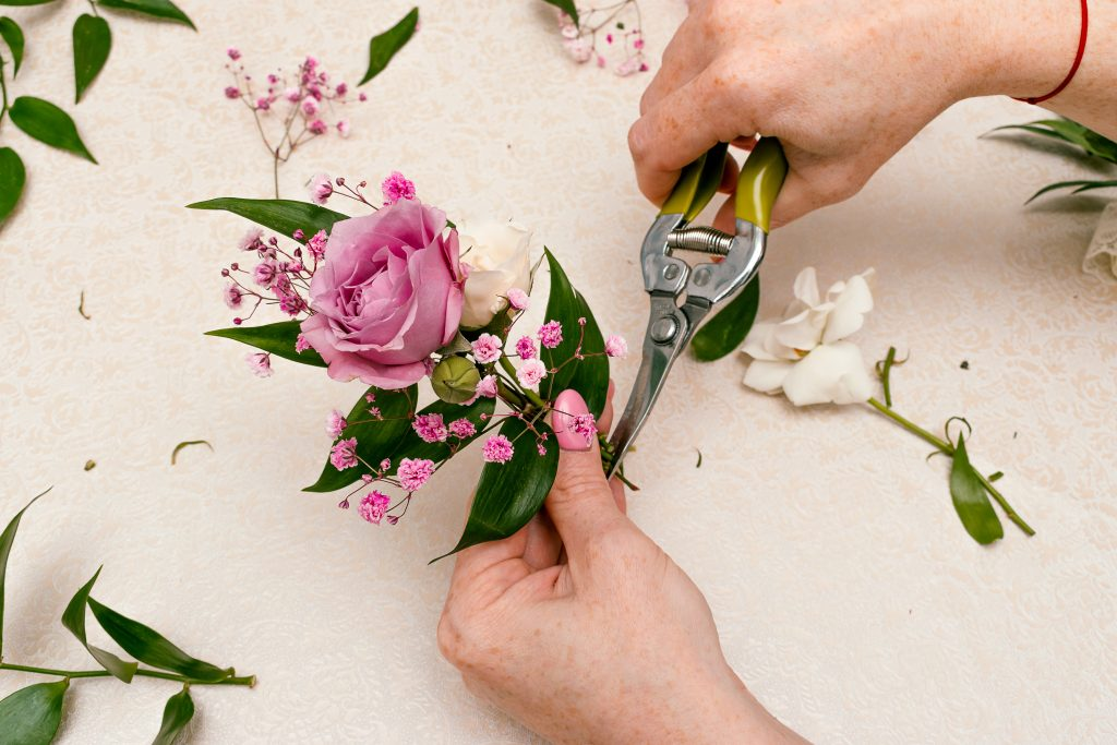 person cutting stems' ends of boutonniere