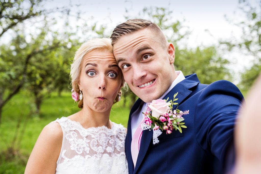 a wedding couple making funny faces and taking a selfie