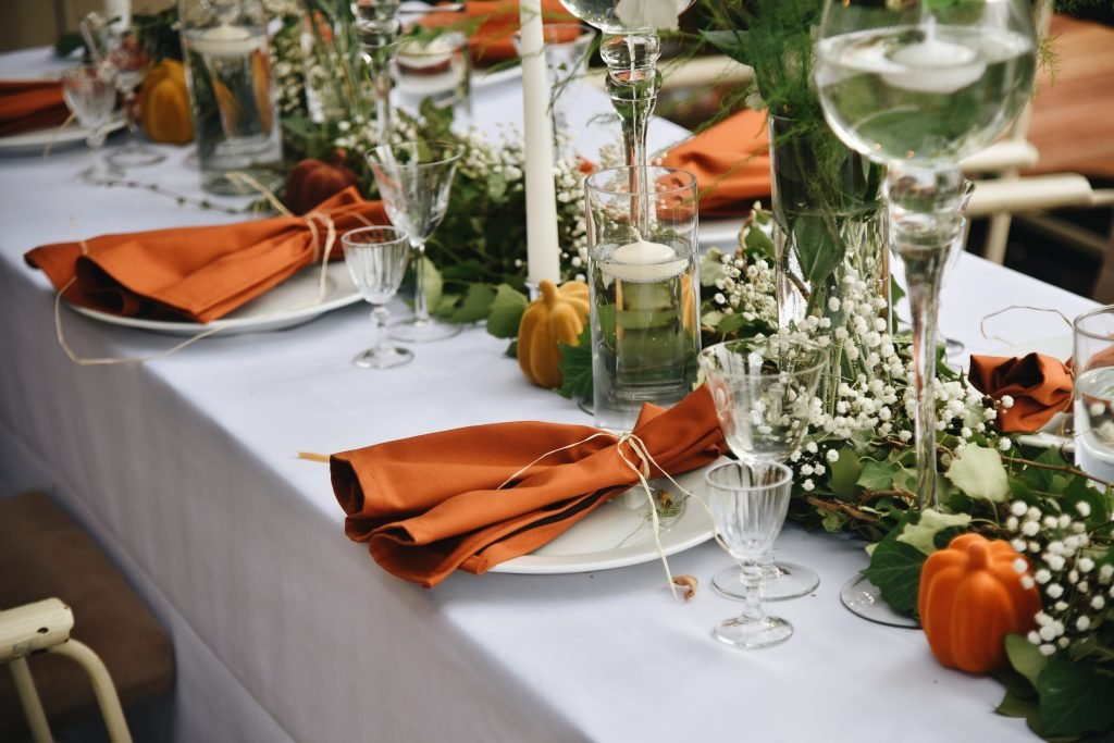 burnt orange wedding napkins and decorative pumpkins displayed on a table