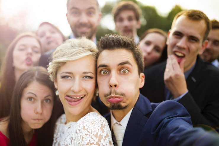 newlyweds taking selfie with their group of friends and making funny faces