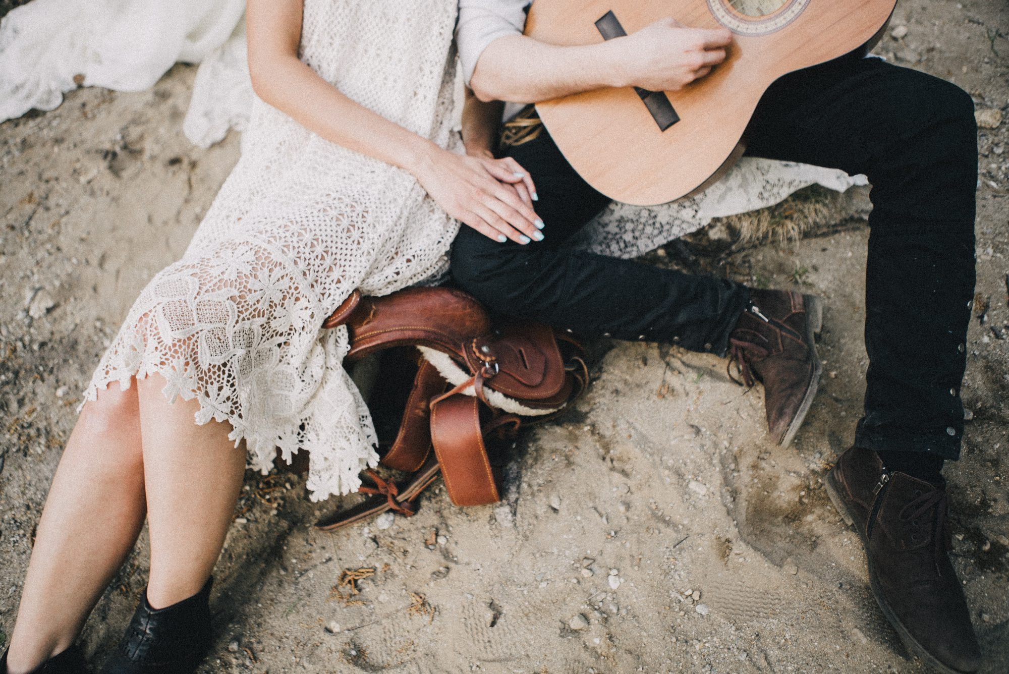 guy playing guitar while girl leans against him