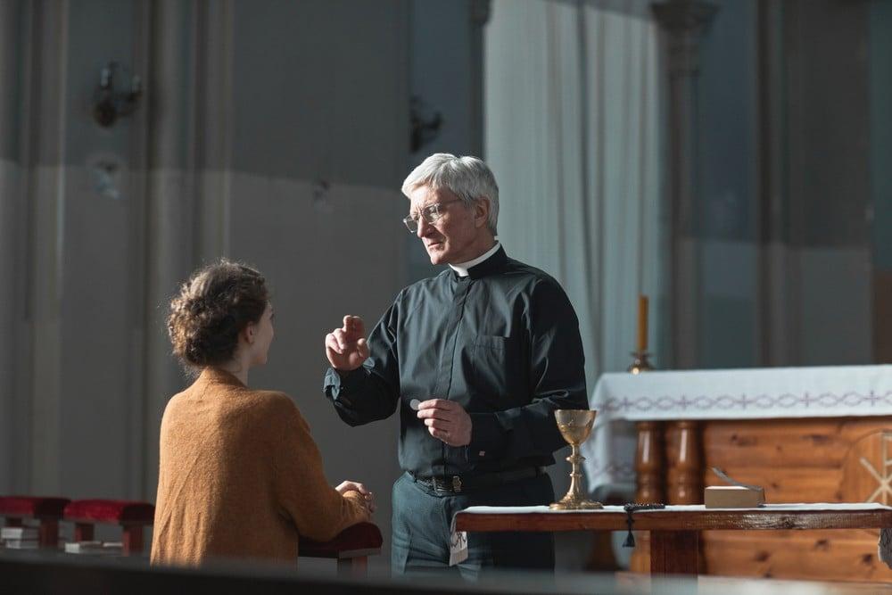 priest talking to woman